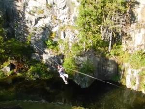 Mann am Schwebeseil über einem Teich. Acrosphere Gerardmer Kletterpark.