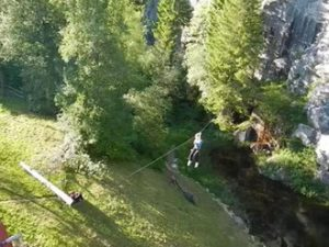 Woman on a zip-line above a lake. Acrosphere.